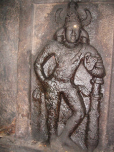 . The right side dvarpala is standing in tribhanga posture, with one hand on his waist and another over his club. Standing with one leg slightly bent, his club is resting on his left side. The club is entwined by a serpent, whose hood is towards the thigh of this dvarpala.